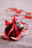 A chocolate egg tied with a red bow