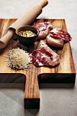 Rohe Geflügelbrust, Coppascheiben, geriebener Pecorino und Pistou auf einem Brett
