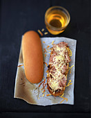 Hotdog mit Andouille-Kaldaunenwurst und Käse überbacken