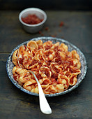 Conchigliette in tomato sauce and flaked raw ham