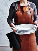 Frau mit Lederschürze hält leere Auflaufformen