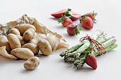 Kartoffeln, grüner Spargel und Erdbeeren auf weißem Untergrund