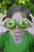 Child playing with green tomatoes