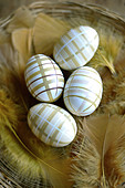 Decorated easter eggs and golden feathers