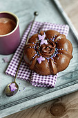 Small chocolate cake with a pink decoration and a cup of expresso