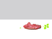 Raw flank steak and peppercorns
