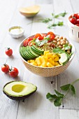 Cherry tomato, mango, chickpea, avocado, semolina and cucumber Oriental Buddha bowl