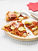 Pizza mit Artischocken, Tomaten und Rohschinken