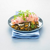 Piece of salmon wrapped in bacon, lentils with carrots