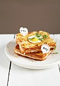 Cheese and ham toasted sandwich and one topped with a fried egg, labels in English