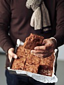 Person holding a tin mould of freshly baked brownies