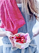Woman holding a punnet of strawberries