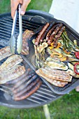 Bacon, sausage and grilled vegetables on the barbecue