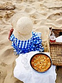 Young girl on the beach with a picnic basket and a banana cake