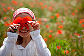 Young girl playing with poppies