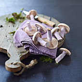 Blue foot mushrooms, mauve cloth and moss on a chopping board