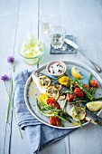 Sea bass with lemon and herbs, grilled vegetables, cream with capers