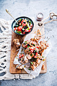 Chicken skewers, tomato salad with two olives
