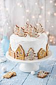 Weihnachtstorte mit Tannenbaum- und Hausförmigen Plätzchen verziert