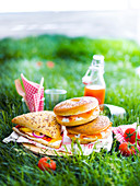 Nordic bagel and chicken, fromage frais and marinated vegetable sandwich for a picnic on the lawn