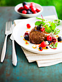 Grilled ostrich fillet with mixed berries and beetroot sprouts
