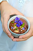 Person holding a chocolate mousse with almonds, hazelnuts, pansies and mint