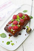 Chocolate cake topped with a fresh raspberries and mint