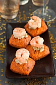 Small carrot cakes topped with shrimps, mayonnaise with capers
