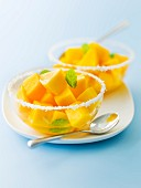 Diced mango fruit salad in mint and coconut syrup