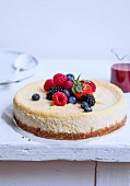 Cheesecake garnished with red berries and coulis