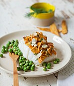 Piece of steamed cod with chanterelle and thinly sliced almond topping and fresh peas