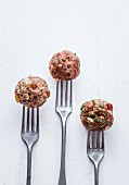 Raw meatball trio on forks