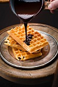 Pouring chocolate sauce onto a pile of Brussels waffles