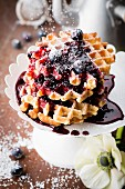 Pile of waffles Liégeoises with blueberry coulis and icing sugar