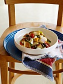 Gnocchis with vegetables, pesto, olives and feta
