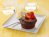 Individual chocolate runny pudding with fresh strawberries and vanilla ice cream