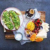 Avocado-rocket lettuce on sliced bread and a dish of fresh fruit