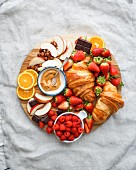 Breakfast tray-style croissant and fresh fruit composition