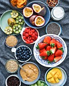 Selection of fresh fruit, dried fruit, cereals, sesame paste to prepare a fruit bowl