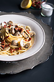 Linguine with clams and sun-dried tomatoes on a black background