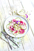 Cucumber, black and pink radish and edible flower salad