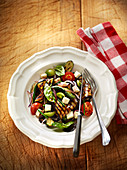 Grilled summer vegetables with diced cheese and basil