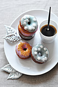 Donuts decorated with icing and a cup of coffee