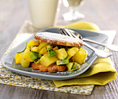 Keks-Sandwich mit fruchtiger Füllung aus Ananas, Kiwi und Limettenzesten