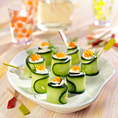 Cucumber rolls garnished with cream cheese and salmon roe