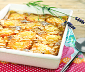 Apricot batter pudding topped with thinly sliced almonds and lavander