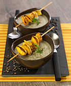 Cream of green lentil soup with mussel brochettes