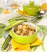 Glazed spring onions with orange and coriander seeds in a casserole dsh