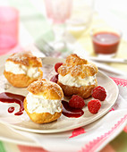 Whipped cream puffs with raspberry coulis