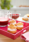 Choux puffs garnished with whipped cream and a jug of raspberry coulis